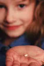 Young girl holding a tooth in her palm